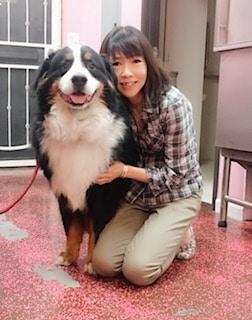 Woof Gang owner kneeling next to a dog